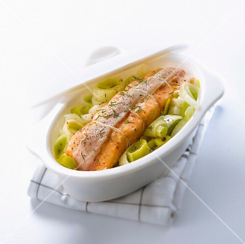 Salmon wrapped in bacon with braised leeks