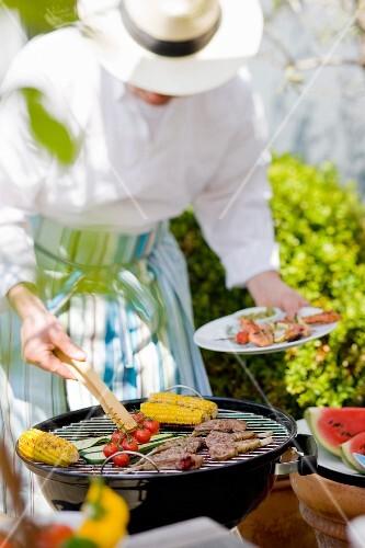 Person cooking on the barbecue outdoors