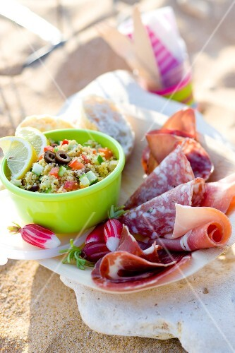 Picnic on the beach with cold cuts and tabbouleh