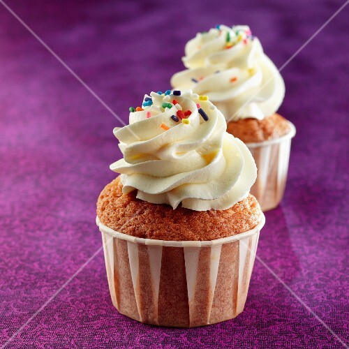 Cupcakes topped with whipped cream and muliticolered sugar drops