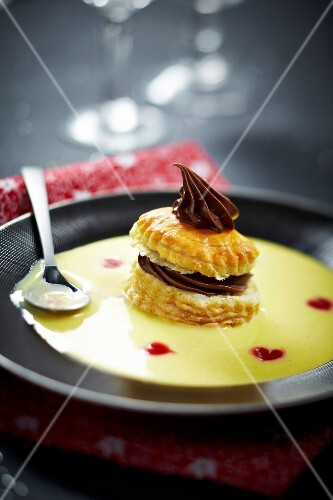 Flaky pastry with chocolate garnish and custard
