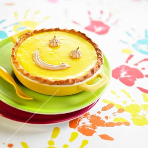 Lemon curd pie decorated with meringue smile