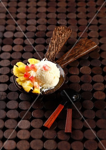 A scoop of coconut ice cream with pineapple and pomegranate carpaccio