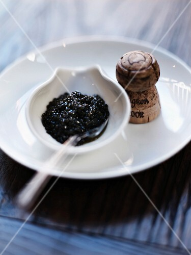 A bowl of caviar and a cork from a bottle of Dom Pérignon