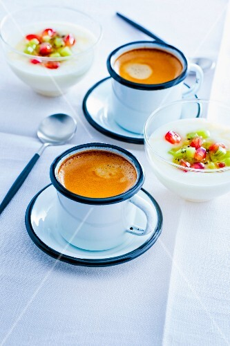 Cups of expresso coffee and a bowl of yoghurt with fresh fruit