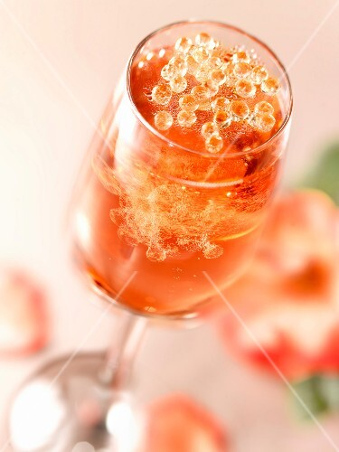 Glass of fizzy rosé wine with pearls