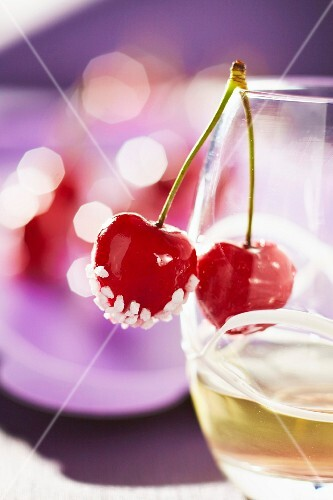 Cherries coated in sugar on the side of a glass