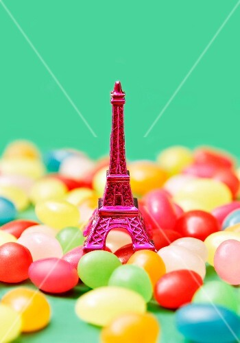 Composition with a mini pink Eiffel Tower and jelly beans on a green background