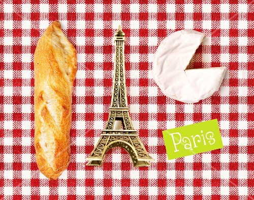 Composition with a mini Eiffel Tower,cheese and bread on a red and white checkered tablecloth