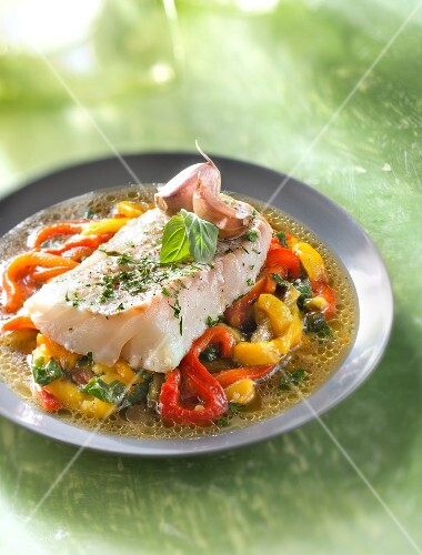 Piece of cod with pink garlic and tarragon on a bed of warm bell pepper salad