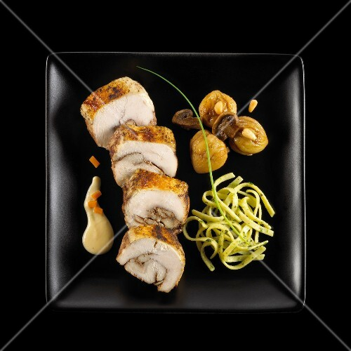 Chicken breast with 5 spices and stuffed with chestnuts and mushrooms on a black background