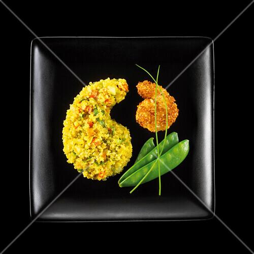 Gebackene Riesengarnele im Sesammantel, gelber Gemüsequinoa und Zuckerschoten auf schwarzem Teller