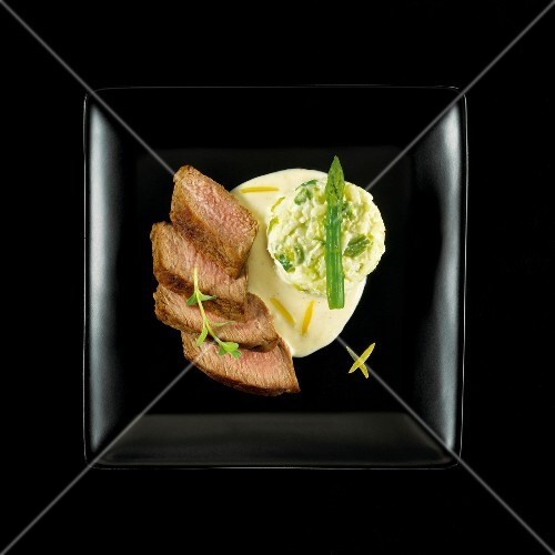 Veal rump,pureed white and green asparagus and creamy lemon sauce on a black background