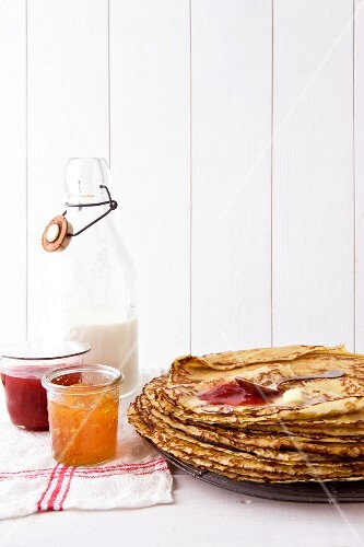 Pile of pancakes and jars of jam