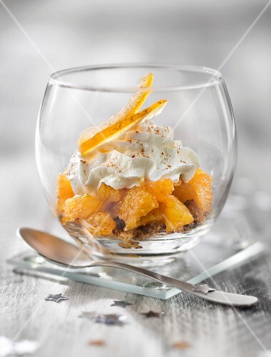 Orange fruit salad with crushed speculos ginger biscuits and whipped cream