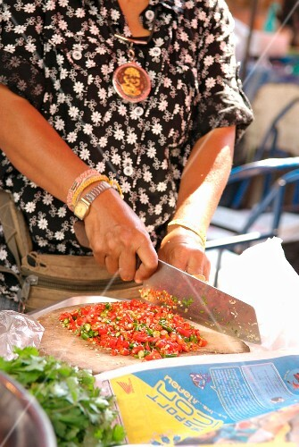Woman preparing peppers in the street