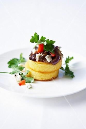 Polenta patties with stewed onions, tomatoes and gorgonzola