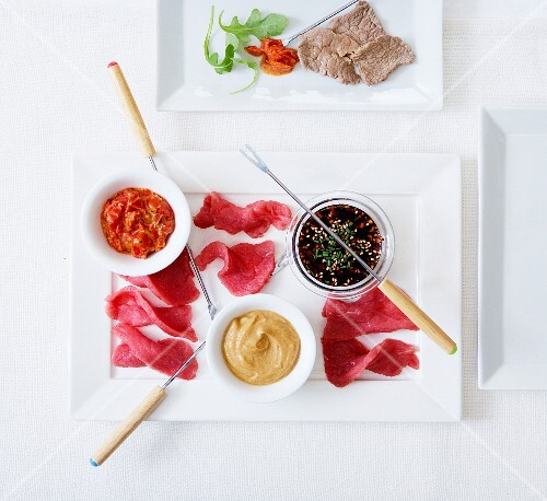 Thinly sliced raw beef with sauces for a Fondue