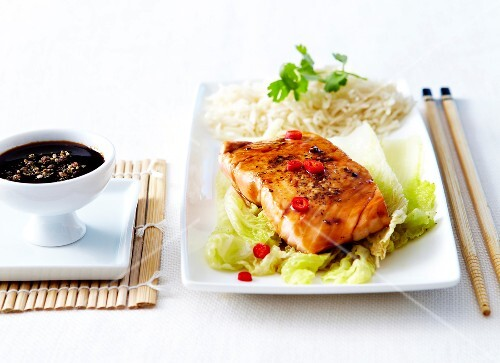 Glazed piece of salmon with soya sauce and red chili peppers