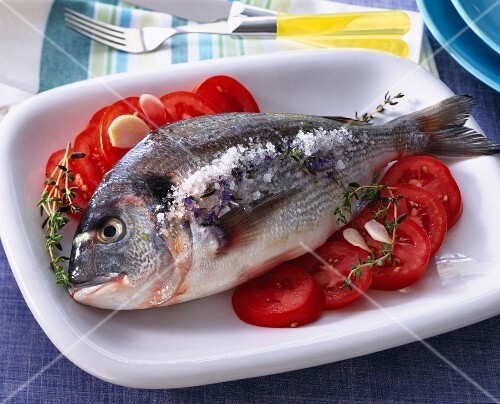 Sea bream with coarse salt, tomatoes with garlic and thyme