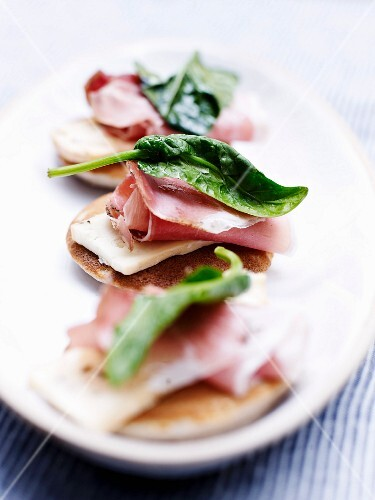 Buckwheat blinis garnished with smoked ham, baby spinch and Munster cheese