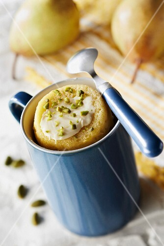 Pear and white chocolate mugcake sprinkled with crushed pistachios