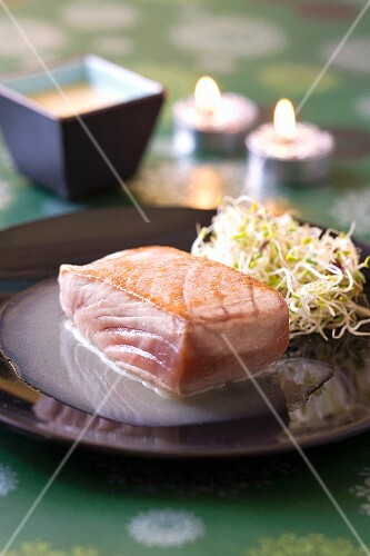 Sweet and sour piece of tuna with sprouts and chocolate sauce