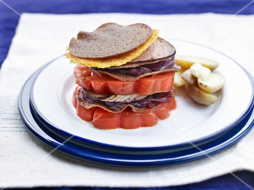 A stack of sliced beefsteak tomatoes, galette, andouille sausage from Guéméné and red cabbage