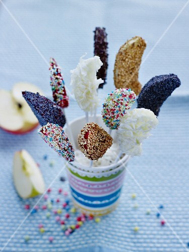 Fruit lollies decorated with colourful sugar sprinkles and seeds