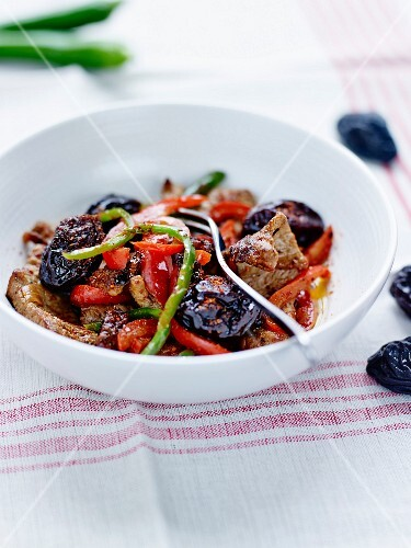 Sautéed pork with baked plums and red and green peppers