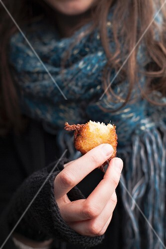Person eating a salt-cod and yam acra