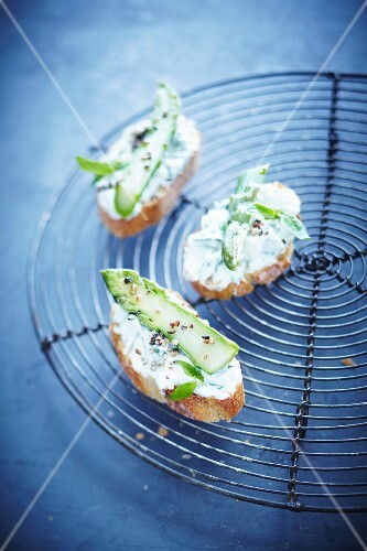 Slices of bread topped with cream cheese and green asparagus