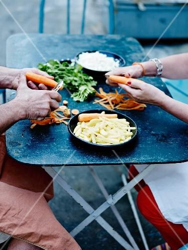 Two people peeling carrots
