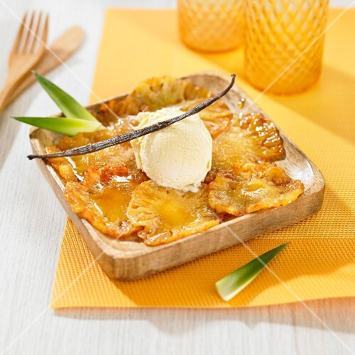 Thin slices of caramelized pineapple and a scoop of vanilla ice cream