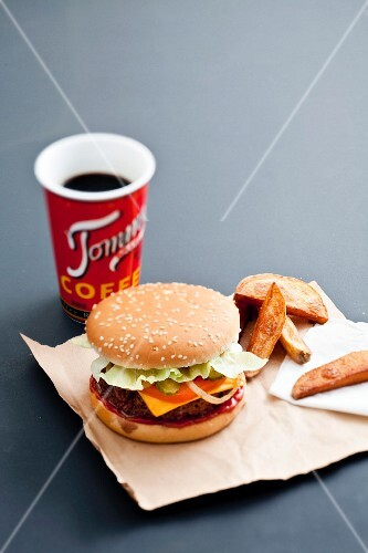 Cheeseburger,fried potatoes and a mug of coffee