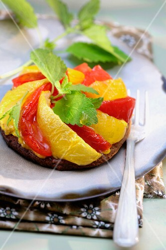 Red and yellow stewed tomato tatin tart with lemon balm