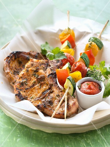 Pork chops marinated with parsley and vegetable brochettes