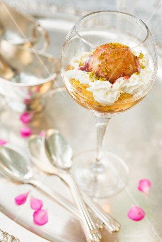 Peach Melba with whipped cream,crushed pistachios and raspberry coulis