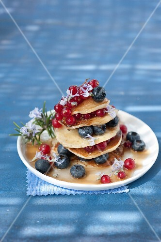 Pancakes with blueberries,redcurrants and maple syrup with rosemary
