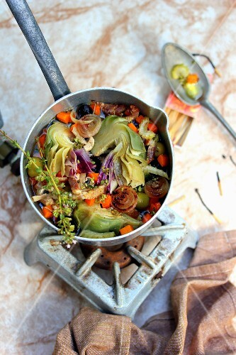 Saucepan of stewed artichokes and vegetables