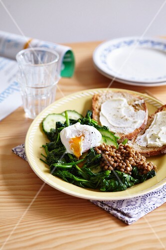 A plate of spinach, cucumber, lentils and a poached egg with toast spread with cream cheese