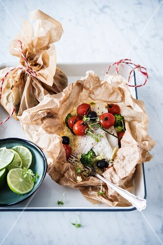 White fish on parchment paper with tomatoes, broccoli, olives and semolina