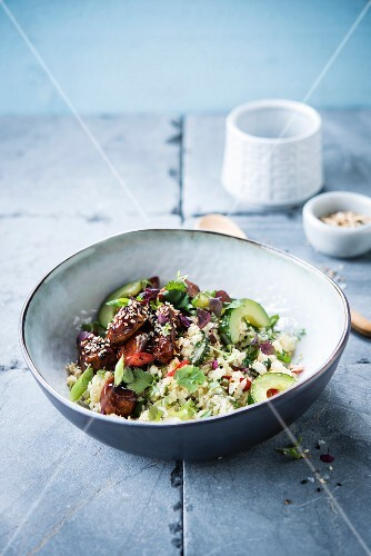 Salad with wheat grass, teriyaki chicken with sesame seeds, cucumber and avocado
