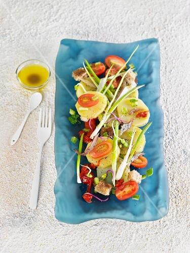 A salad of potatoes, tomatoes, mackerel and fresh onions