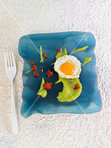 A fried egg with guacamole and red tapenade