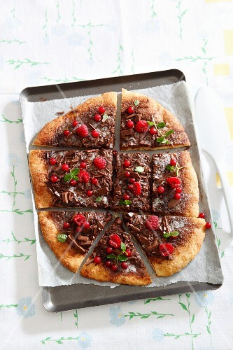 A sweet pizza with chocolate, redcurrants, raspberries and mint