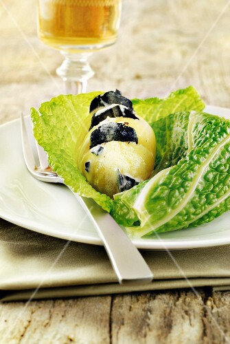 Potato papillote with black truffles on a savoy cabbage leaf