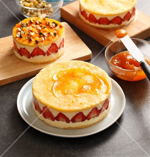A strawberry cream cake being spread with apricot jam