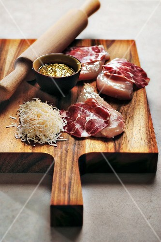 Chicken breasts, sliced coppa, grated pecorino cheese and pistou on a chopping board