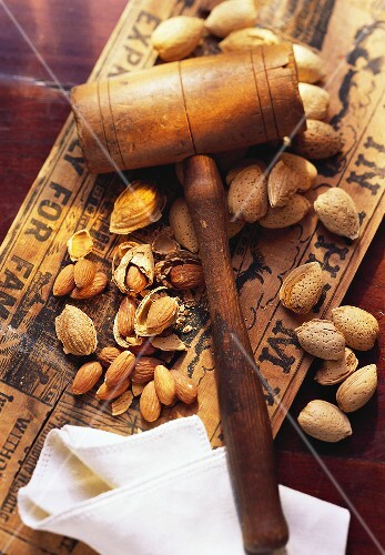 Whole and Shelled Almonds with a Wooden Hammer Nut Cracker